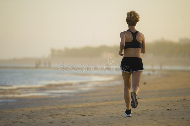 Back view of young happy and attractive fit woman running on the beach in outdoors jogging workout in fitness training and healthy stock image