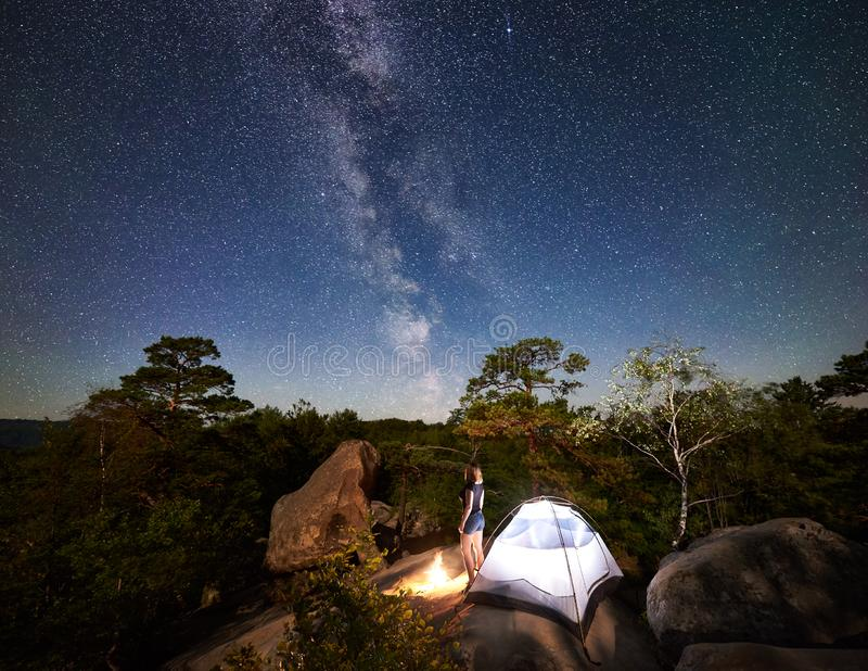 Woman resting beside camp, bonfire and tourist tent at night stock photo