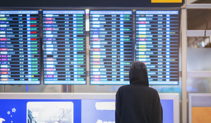 Back view of young man in airport near flight timetable, hacker background of departure board at airport. Ok royalty free stock photography