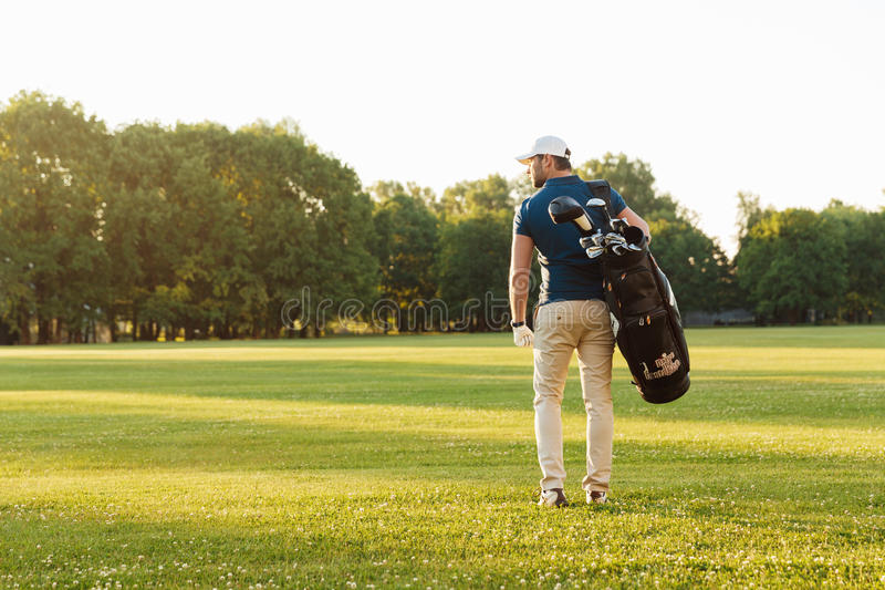 Back view of young man in cap carrying golf bag royalty free stock photography