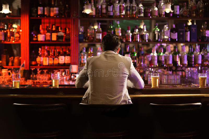 Back view of a young man drinking beer stock images