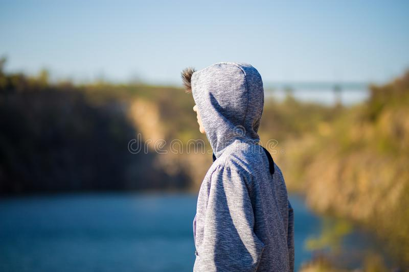 Back view of young man looking at the beautiful view at the lake. Travel and psychology concept. royalty free stock photos