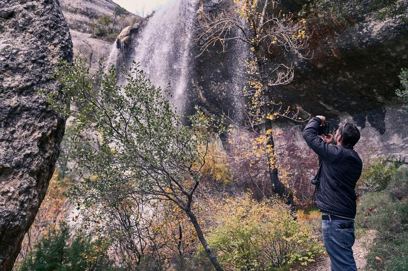 Back view of a young man taking a picture of a waterfall. With his smartphone stock image