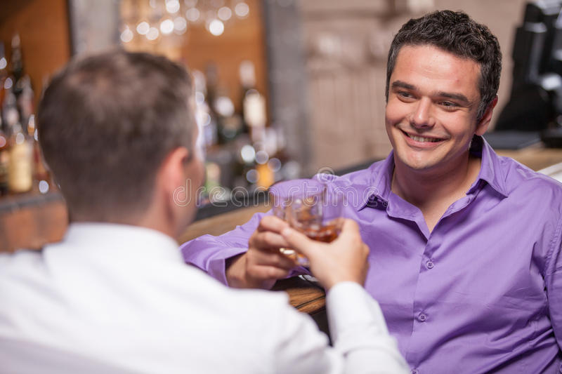Back view of young man talking at counter. stock image