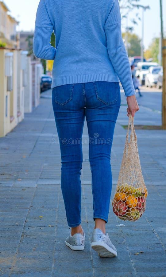 Back view young modern woman walking down a street royalty free stock photo