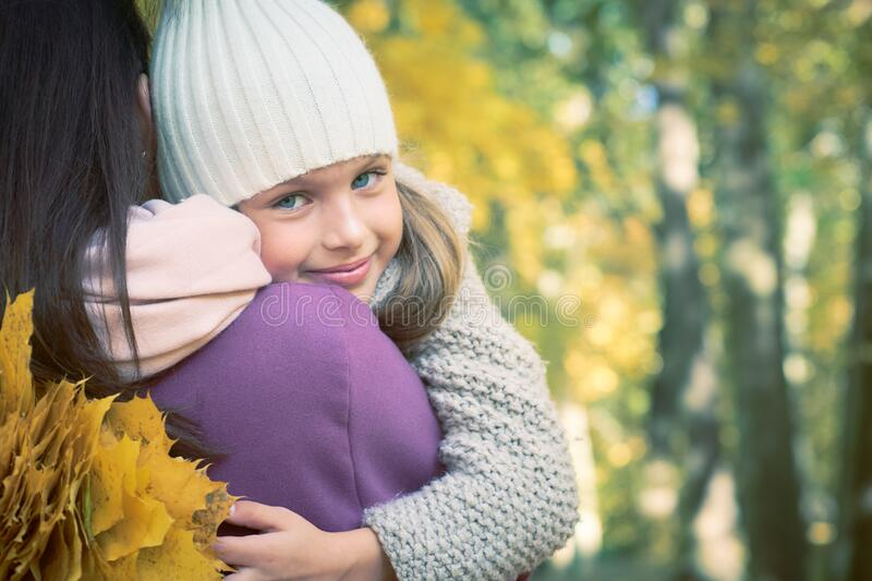 Back view on young mom and cute toddler girl hugging in the autumn public park. Family love concept. Back view on young mom and cute toddler girl hugging in the royalty free stock photo