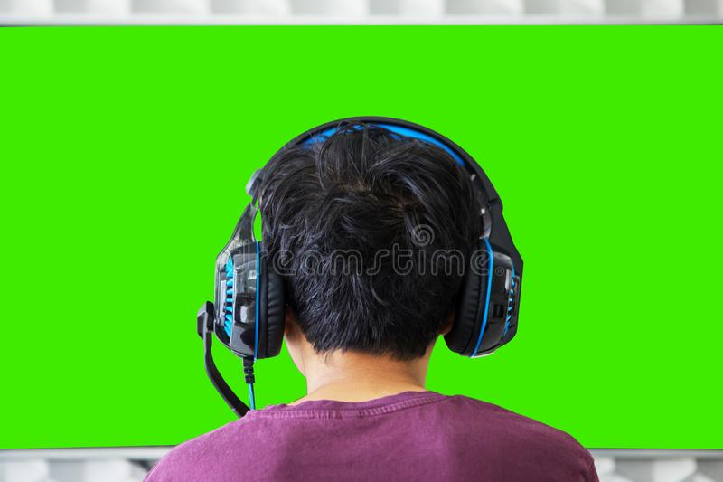 Young preteen boy watches TV with headphone stock images