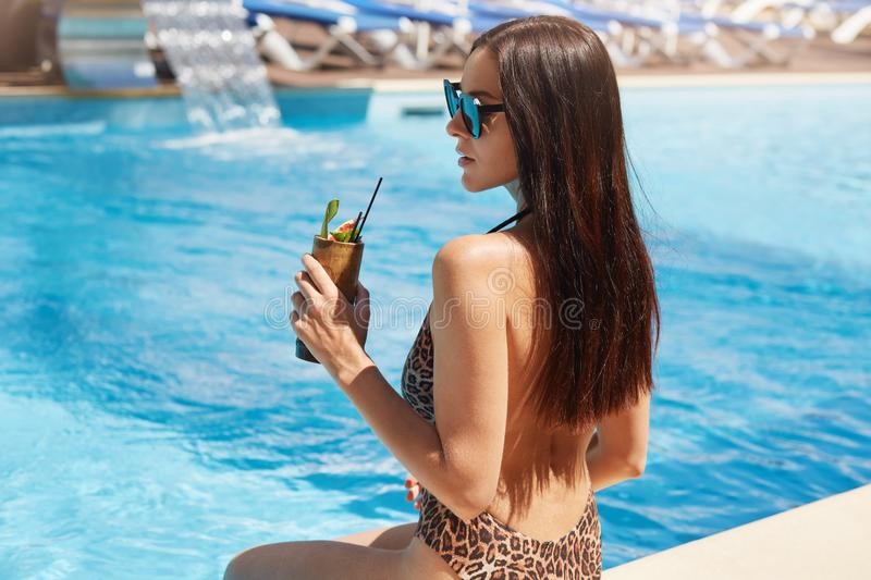 Back view of young pretty woman drinking cocktail against outdoor pool. Female with perfect tanned skin sitting near swimming pool royalty free stock photo