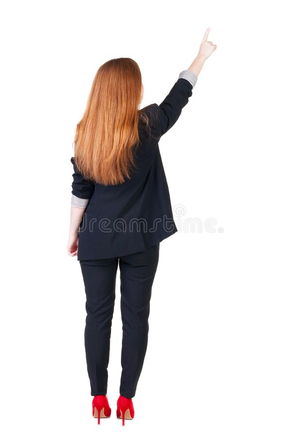 Back view of young redhead business woman pointing at wal stock images