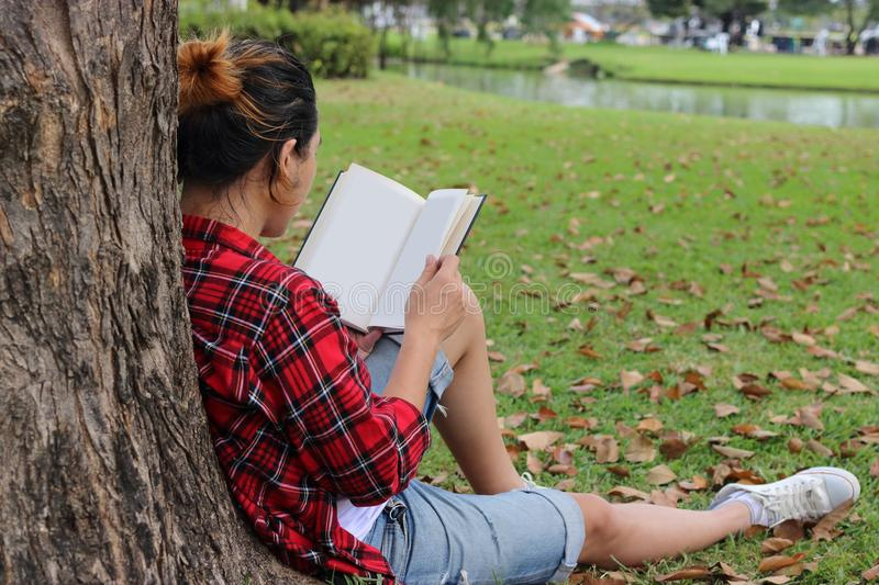 Back view of young relaxed man in red shirt leaning against a tree and reading textbook in beautiful outdoor park. stock photos