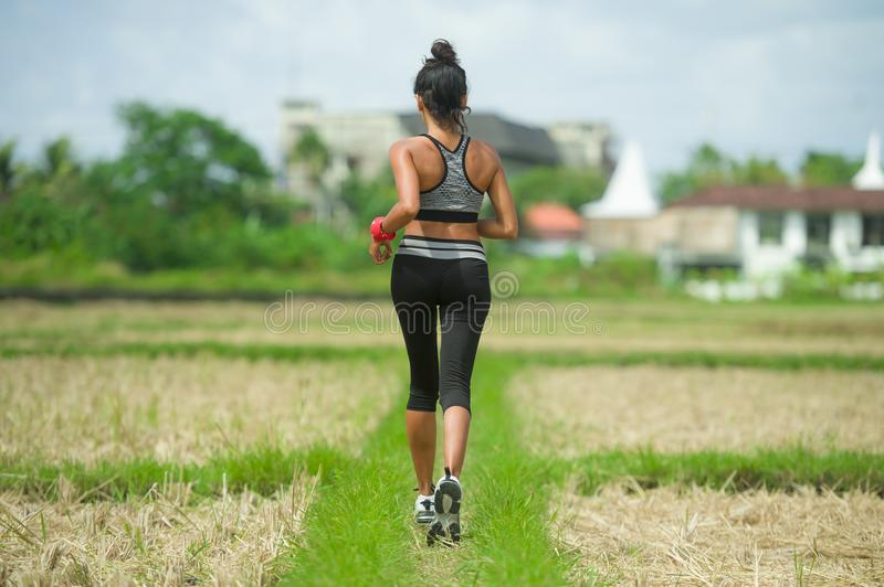 Back view of young runner woman with attractive and fit body in running outdoors workout at beautiful off road track green landsca royalty free stock image