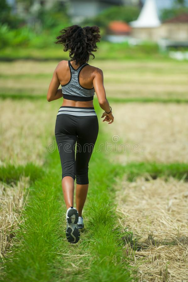 Back view of young runner woman with attractive and fit body in running outdoors workout at beautiful off road track green landsca stock photo
