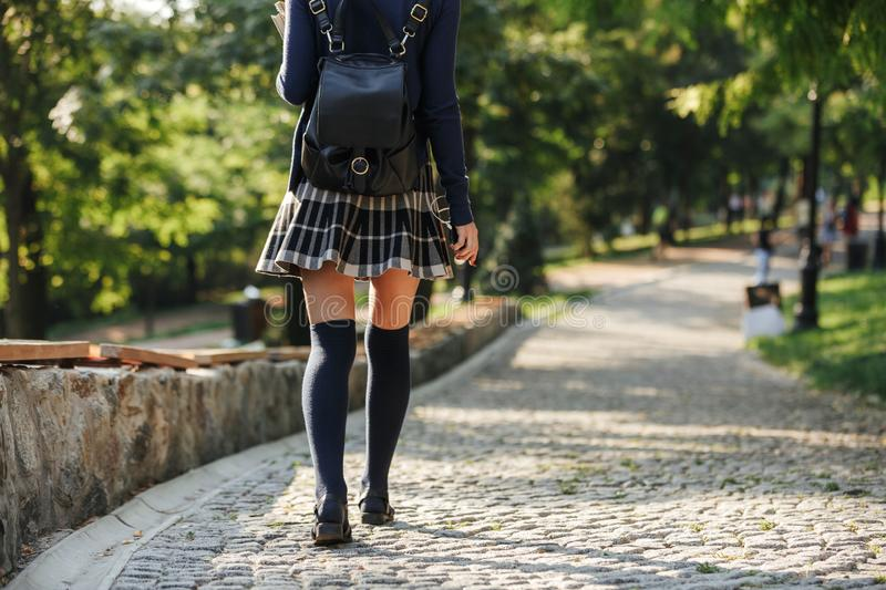 Back view of a young school girl carrying backpack stock photography