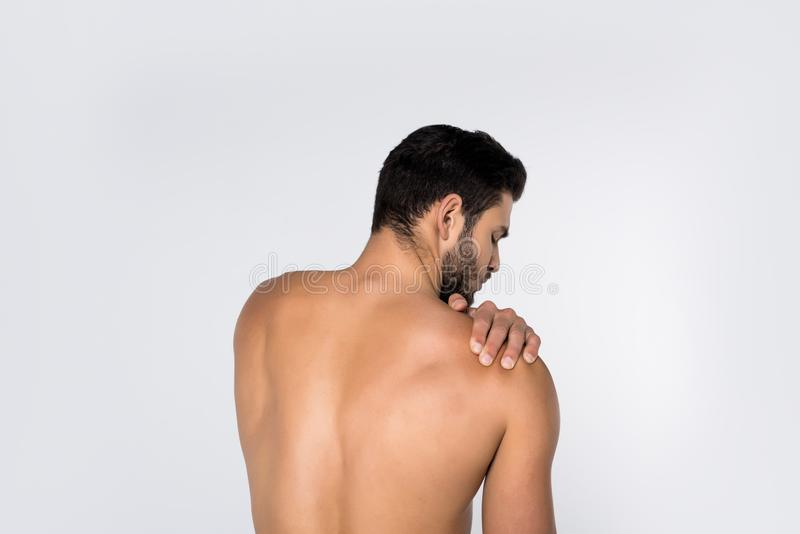 back view of young shirtless man with pain in shoulder stock photos