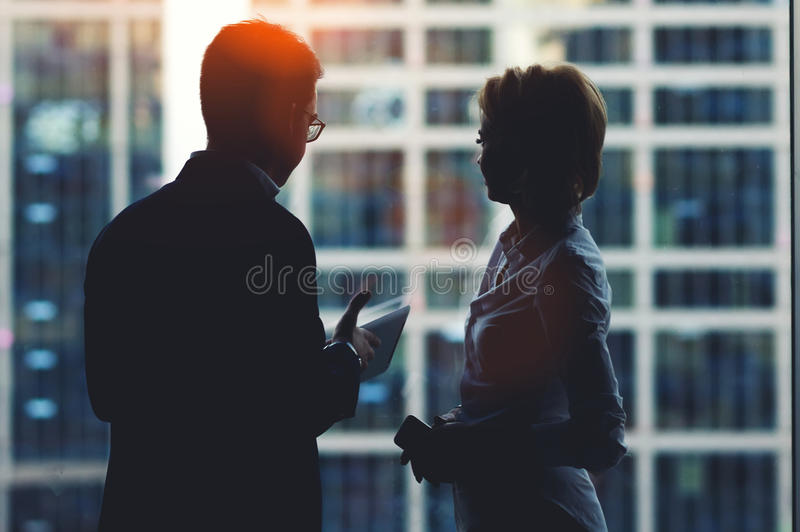 Back view of young successful man and woman financiers standing with digital tablet and mobile phone in office interior. Two colleagues having conversation stock photos