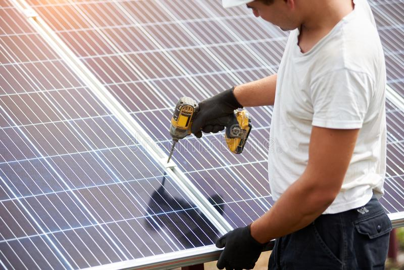 Installation of stand-alone exterior photo voltaic panels system. Renewable green energy generation. Back view of young technician in helmet connecting solar royalty free stock photos