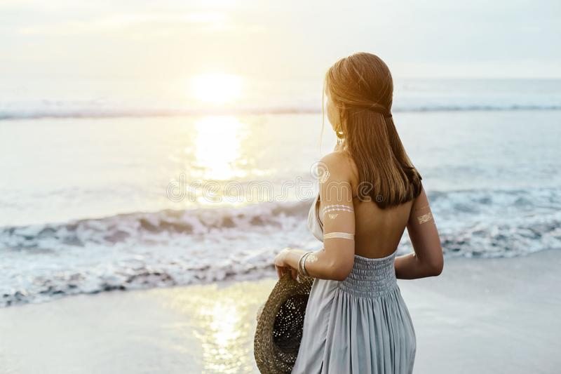 Young teenage girl thinking while looking at horizon on sunset. Back view of young teenage girl thinking while looking at horizon over shore on sunset stock image