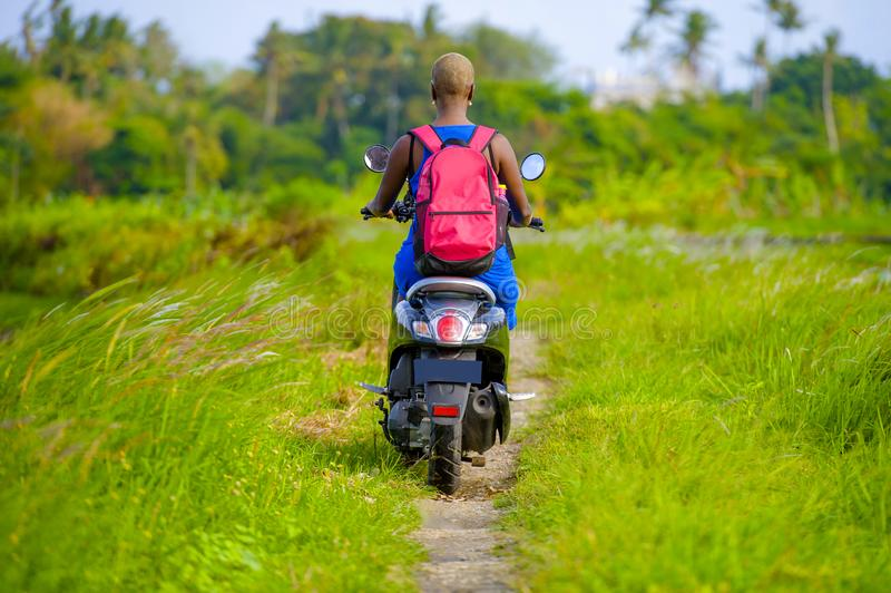 Back view of young tourist afro American black woman riding motorbike happy in beautiful Asia countryside along green rice fields. Back view of young tourist royalty free stock photos
