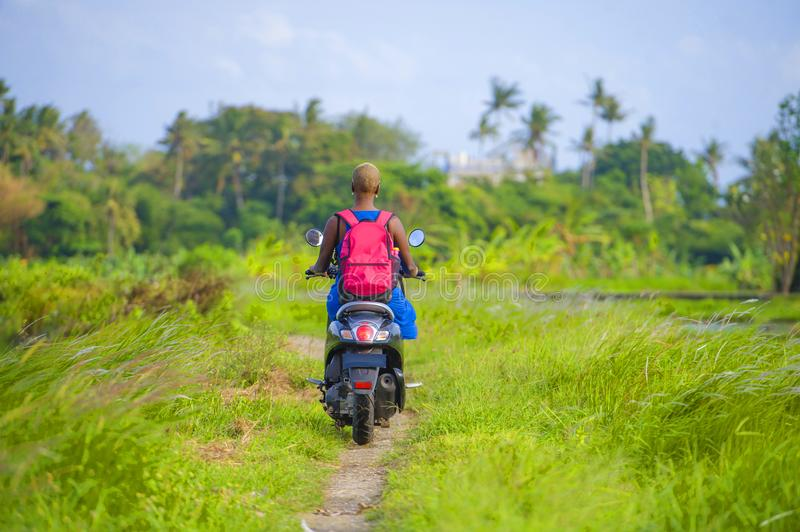 Young attractive tourist afro American black woman riding motorbike happy in beautiful Asia countryside along green rice fields s. Back view of young tourist royalty free stock photography