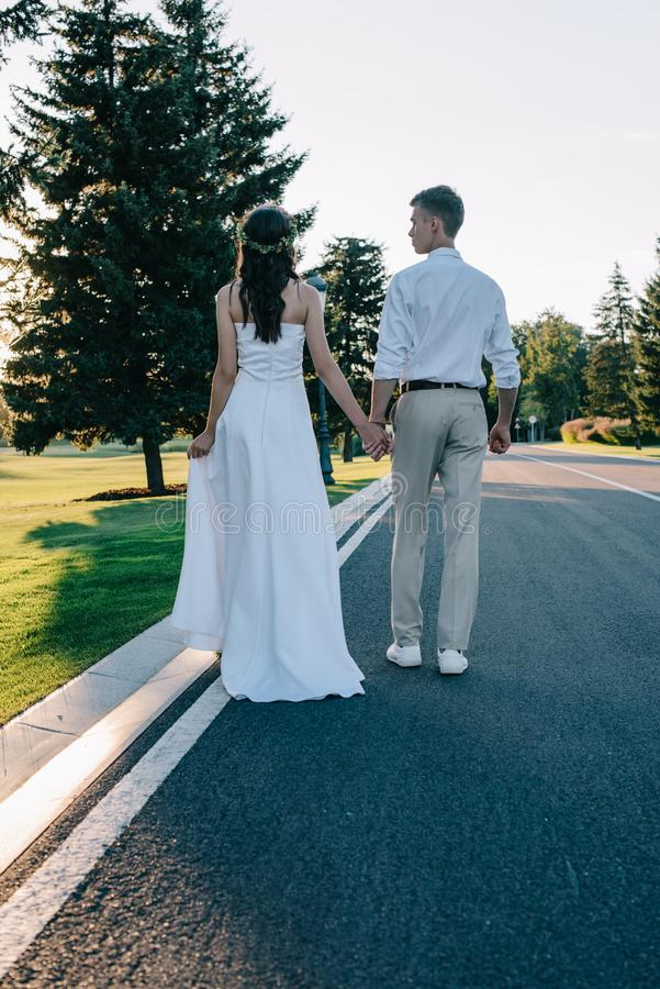 back view of young wedding couple holding hands and walking on walkway royalty free stock images