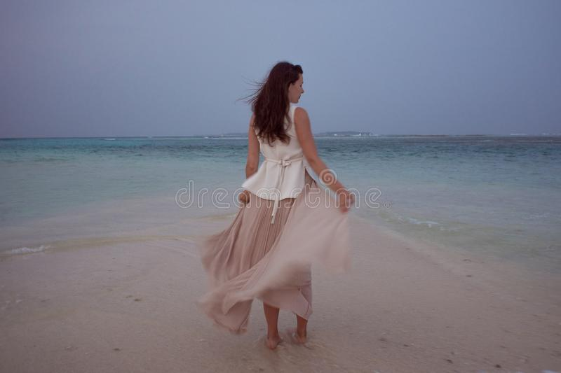 Back view of young woman against a sea horizon. Brunette girl in white skirt flying on wind. On a background of a sea royalty free stock photo