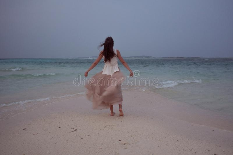 Back view of young woman against a sea horizon. Brunette girl in white skirt flying on wind. Back view of young woman against a sea horizon. Brunette girl in stock images
