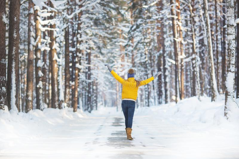 Back view of young woman in a bright clothes walks on a road in a winter forest stock images