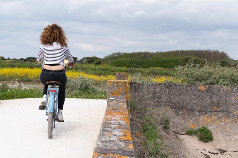 Back view young woman cycling at seaside on island Ile de Re in west France royalty free stock image