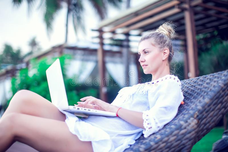Back view of young woman doing remote work at modern laptop while resting on sun bed near blue swimming pool enjoying summer stock image
