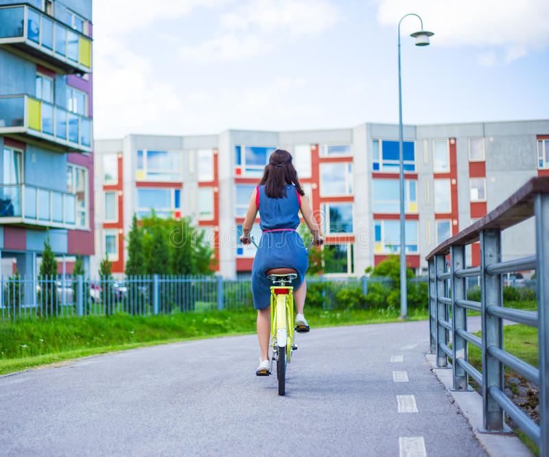 Back view of young woman in dress riding vintage bicycle. In the street stock photography
