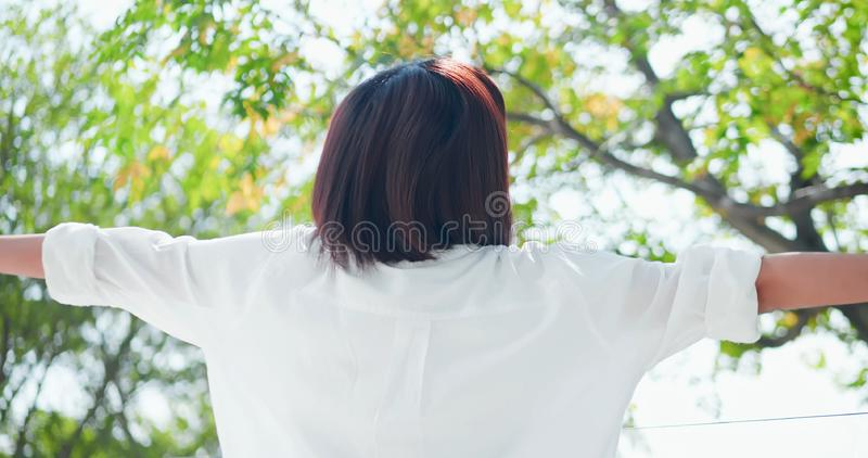 Young woman feel carefree. Back view of young woman feel carefree and take a deep breath at nature outdoor stock photography
