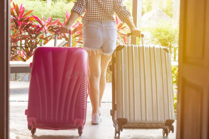 Young woman with suitcase walking away through the open door. Woman walking away back view in a denim shorts and snickers. royalty free stock photo