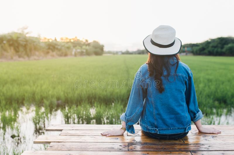 Back view of young woman in hat. Girl enjoying at beautiful nature with sunset. Travel Summer Holiday Vacation and Relaxation royalty free stock photos