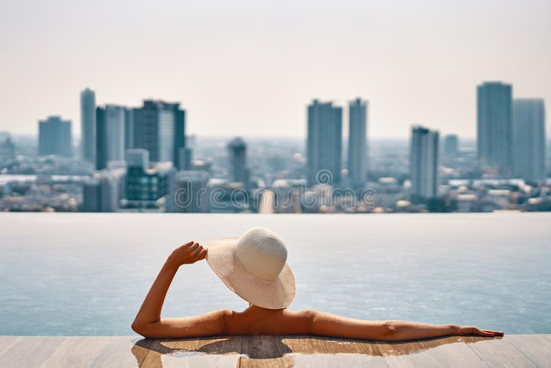 Back view of young woman in hat relaxing in swimming pool on the roof top of hotel and enjoy cityscape stock images