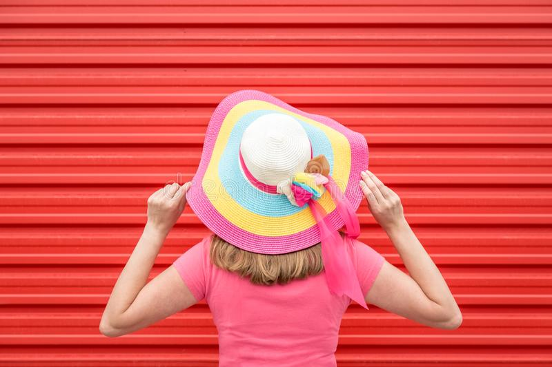 Back view of young woman with multicolored straw hat. Summer vacation creative concept. stock photo