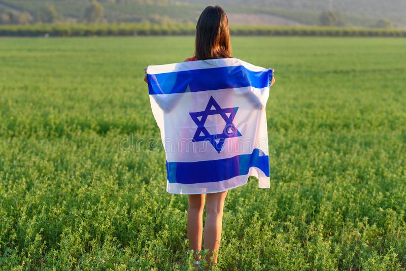 Jewish girl with flag of Israel on amazing landscape in beautiful summer. royalty free stock photography