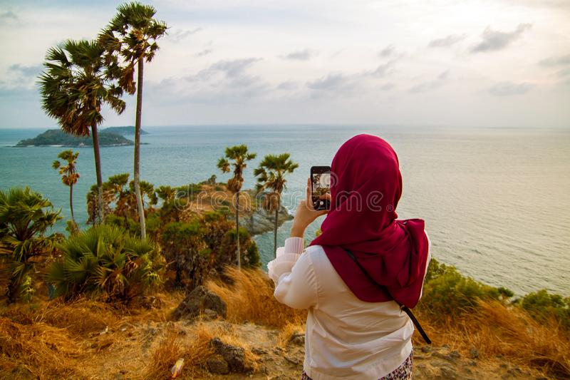 Back view of young woman photographing the mountain landscape by smartphone camera at the sunset over the Sea. royalty free stock photo