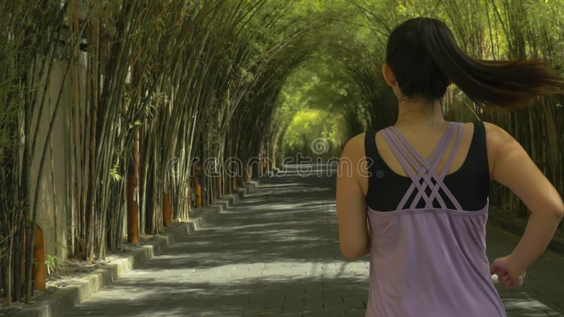 Back view of young woman with pony tail running practicing jogging workout at beautiful city park in healthy lifestyle and sport stock photos