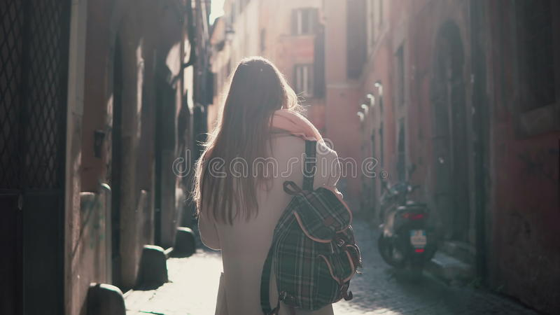 Back view of young woman walking at city street in Europe at morning. Girl exploring the old town alone, looking around. royalty free stock photo