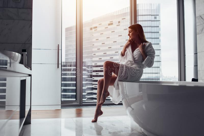 Back view of young woman wearing white bathrobe standing in bathroom looking out the window with bathtub in foreground stock images