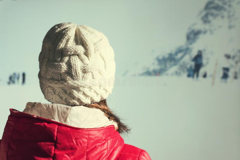 Back view of young woman in a winter knitted white cap, red jacket against the backdrop of the snowy mountains. Back view of young woman in a winter knitted stock photos
