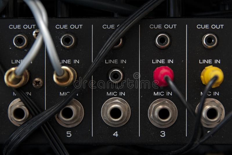 Back of a vintage mixing console with cables connected to the plugs stock image