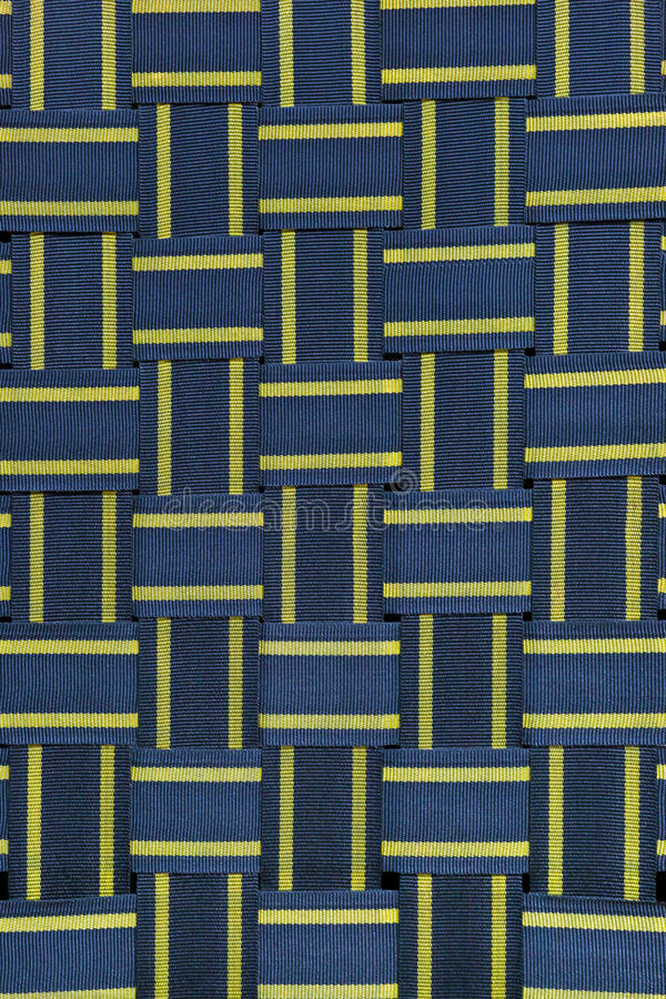 Back of wicker chair closeup. Texture of seat back, cross woven of striped blue-and-yellow coarse cloth stock images