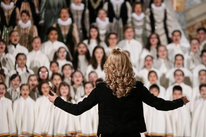 Back of a woman conducting a choir of children royalty free stock photos