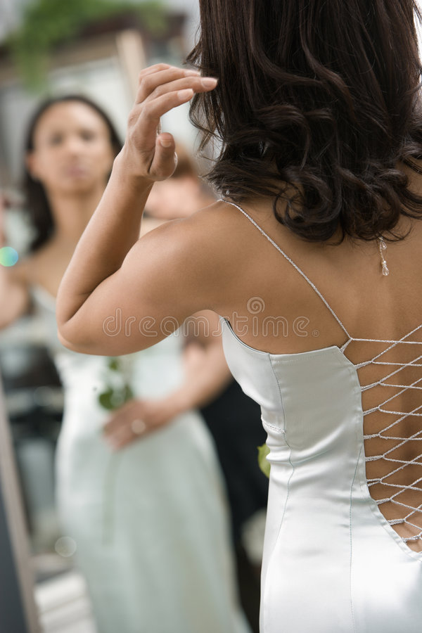 Back of woman in gown. Back of African-American woman in evening gown looking at mirror stock images