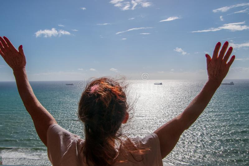Back of woman with long red hair looking out at a calm flat ocean with her arms up in the air. royalty free stock photography