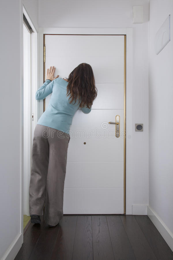 Back woman looking at peephole. Brown trousers green jersey woman back looking to peephole interior house hall white door wooden floor royalty free stock image