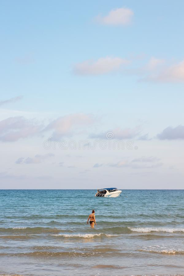 Back of a woman wearing bikini standing in the sea with speed boats and bright sky in background at Koh Mak Island in Trat. royalty free stock photography