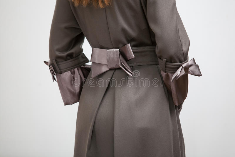 Back of the women coat with silk bow. Photo of back of the woman coat with silk bow stock image