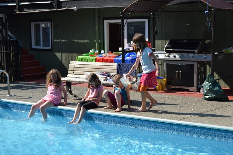Back yard pool party. Young girls sit around the pool at a back yard birthday party royalty free stock image